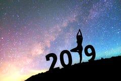 Mostre em silhueta a ioga feliz da jovem mulher para o fundo o do ano 2019 novo Fotografia de Stock