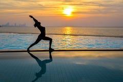 Mostre em silhueta a ioga praticando da jovem mulher na piscina e na praia no por do sol fotos de stock