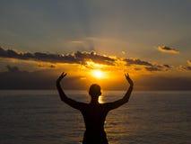 Mostre em silhueta a ioga praticando da jovem mulher na praia no por do sol Conceito vivo e ativo saudável do resto foto de stock