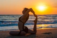 Mostre em silhueta a ioga praticando da jovem mulher na praia no por do sol ou no alvorecer Foto de Stock Royalty Free