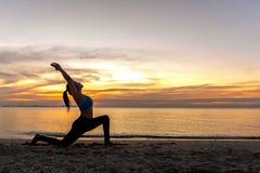 Mostre em silhueta a jovem mulher o exercício do estilo de vida que vital medita e bola praticando da ioga na praia foto de stock