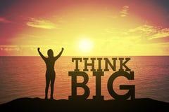 Mostre em silhueta a jovem mulher que levanta-se e que levanta sua mão sobre o conceito do vencedor no texto GRANDE THINK sobre u Fotos de Stock Royalty Free
