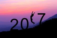 Mostre em silhueta a jovem mulher que salta sobre 2017 anos no monte na SU Fotografia de Stock