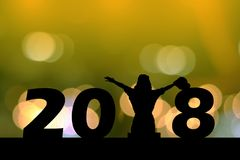 Mostre em silhueta a jovem mulher que senta-se na terra, 2018 anos novos Imagens de Stock