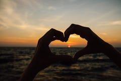 Mostre em silhueta a mão na forma do coração com nascer do sol no meio e no fundo da praia Fotografia de Stock Royalty Free