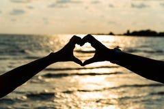 Mostre em silhueta a mão na forma do coração com nascer do sol no meio e seja Foto de Stock Royalty Free