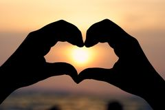 Mostre em silhueta a mão na forma do coração com nascer do sol no meio e na praia como o conceito do Valentim do fundo com espaço Imagem de Stock Royalty Free