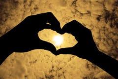 Mostre em silhueta a mão na forma do coração em um céu alaranjado Foto de Stock Royalty Free