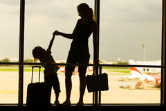 Mostre em silhueta a mãe com seu filho que está na janela no ar Imagem de Stock