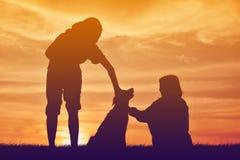 Mostre em silhueta a menina bonito com as mulheres e o cão que jogam no por do sol do céu Fotografia de Stock