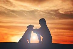 Mostre em silhueta a menina bonito e o cão que jogam no por do sol do céu Imagens de Stock Royalty Free