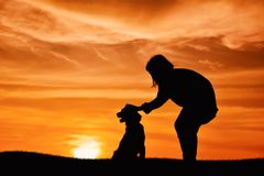 Mostre em silhueta a menina bonito e o cão que jogam no por do sol do céu Imagem de Stock Royalty Free