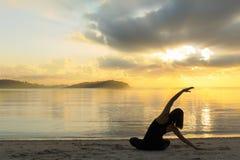 Mostre em silhueta a menina da ioga no nascer do sol na praia imagens de stock royalty free