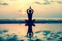 Mostre em silhueta a mulher da ioga na praia do mar no por do sol relaxe Fotografia de Stock Royalty Free