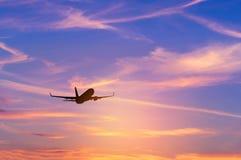 Mostre em silhueta o avião do passageiro que voa afastado dentro à altura muito ao alto durante o tempo do por do sol imagem de stock royalty free