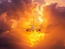 Mostre em silhueta o avião do passageiro que voa afastado dentro à altura muito ao alto durante o tempo do por do sol Fotos de Stock Royalty Free