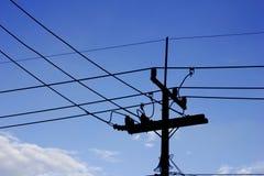 Mostre em silhueta o cargo da eletricidade com fundo do céu prendido e azul Foto de Stock
