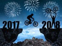 Mostre em silhueta o ciclista que salta no ano novo 2018 Fotos de Stock