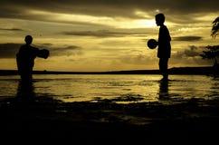 Mostre em silhueta o conceito da imagem do menino que joga na praia durante a água da maré baixa Imagens de Stock