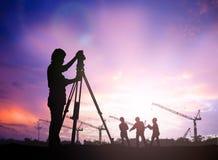 Mostre em silhueta o coordenador da avaliação que trabalha em um terreno de construção sobre o borrão Foto de Stock