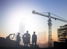 Mostre em silhueta o coordenador em um terreno de construção sobre o constructio borrado Imagem de Stock