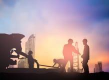Mostre em silhueta o coordenador que trabalha em um terreno de construção sobre o engodo borrado Imagem de Stock