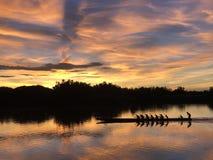 Mostre em silhueta o enfileiramento do grupo de pessoas no barco a remos longo no rio em nuvens claras crepusculares bonitas do c foto de stock royalty free