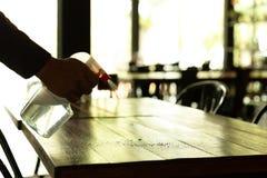 Mostre em silhueta o garçom que limpa a tabela com o pulverizador desinfetante em um restaurante fotografia de stock royalty free