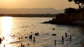 Mostre em silhueta o grupo de alegria do viajante que reraxing e que salta no beira-mar no tempo do por do sol, pessoa da praia d vídeos de arquivo