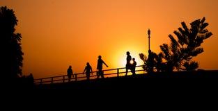 Mostre em silhueta o grupo de pessoas no exercício da atividade, passeio, correndo na passagem no beira-rio, e no céu bonito do p Fotografia de Stock Royalty Free