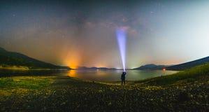 Mostre em silhueta o homem com lanterna elétrica e a galáxia da Via Látea no lago foto de stock