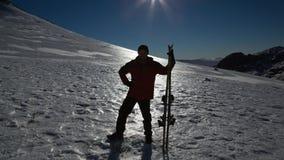 Mostre em silhueta o homem com a placa do esqui que está na neve Foto de Stock Royalty Free