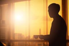 mostre em silhueta o homem de negócios que guarda o copo de café que olha para fora sobre o c Imagem de Stock