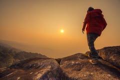 Mostre em silhueta o homem que anda no céu do por do sol Fotografia de Stock