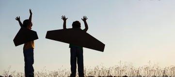 Mostre em silhueta o menino com as caixas de cartão das asas contra o sonho o do céu imagens de stock
