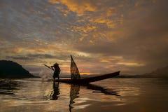 Mostre em silhueta o pescador do lago Bangpra na ação ao pescar Foto de Stock Royalty Free