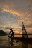 Mostre em silhueta o pescador do lago Bangpra na ação ao pescar Fotos de Stock Royalty Free