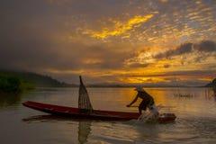Mostre em silhueta o pescador do lago Bangpra na ação ao pescar Fotos de Stock