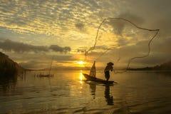 Mostre em silhueta o pescador do lago Bangpra na ação ao pescar Imagem de Stock Royalty Free