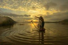 Mostre em silhueta o pescador do lago Bangpra na ação ao pescar, Fotos de Stock Royalty Free