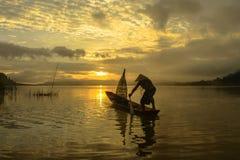 Mostre em silhueta o pescador do lago Bangpra na ação ao pescar, Tha Fotografia de Stock