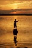 Mostre em silhueta o pescador do lago na ação ao pescar Fotografia de Stock