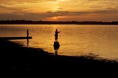 Mostre em silhueta o pescador do lago na ação ao pescar Fotos de Stock