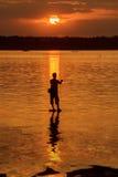 Mostre em silhueta o pescador do lago na ação ao pescar Imagem de Stock Royalty Free