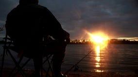 Mostre em silhueta o pescador que senta-se na cadeira durante a pesca da noite no rio vídeos de arquivo
