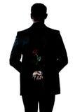 Mostre em silhueta o retrato do homem que prende uma flor da rosa Foto de Stock Royalty Free