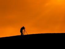 Mostre em silhueta o tiro de um fotógrafo que toma uma foto Imagem de Stock