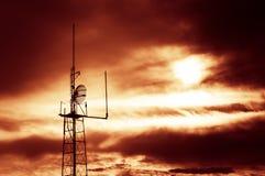 Mostre em silhueta o tiro do pilão da antena de rádio da televisão com nuvens Fotografia de Stock Royalty Free