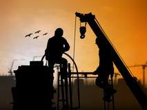 Mostre em silhueta o trabalhador no canteiro de obras sobre a construção borrada Imagem de Stock Royalty Free