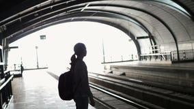 Mostre em silhueta o trem de espera na estação aberta, sumário do mochileiro da menina do turista do curso video estoque